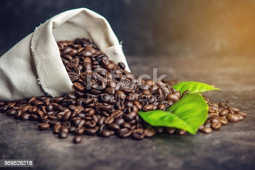 istock Pile of coffee beans and green leaves in bag on dark background 959526218