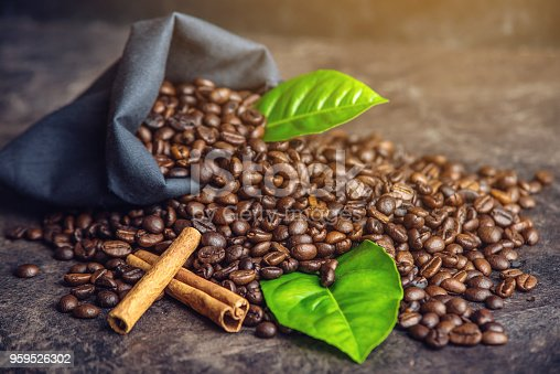 istock Pile of coffee beans and green leaves in bag on dark background 959526302