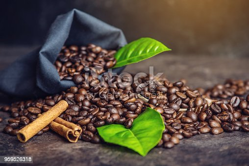 istock Pile of coffee beans and green leaves in bag on dark background 959526318