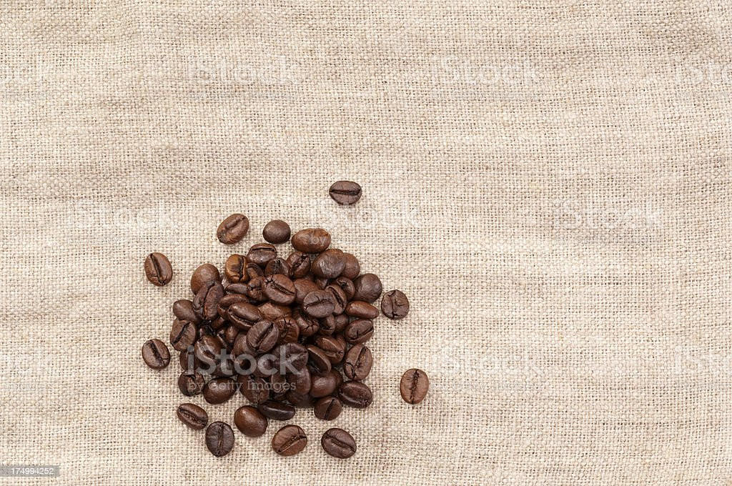 Pile of coffee beans on fabric macro royalty-free stock photo