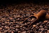 Pile of coffee beans with wooden scoop, close up, dark background with copy space, shallow depth of field