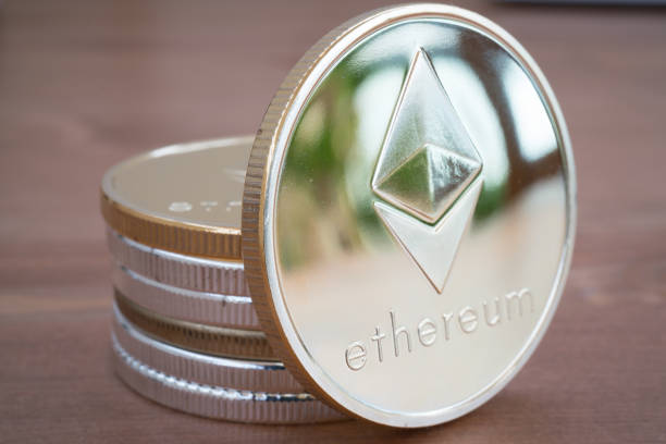 Pile of Coin of Silver Ethereum on wooden background stock photo