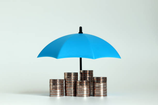 una pila di monete con un ombrello blu aperto. - protezione foto e immagini stock