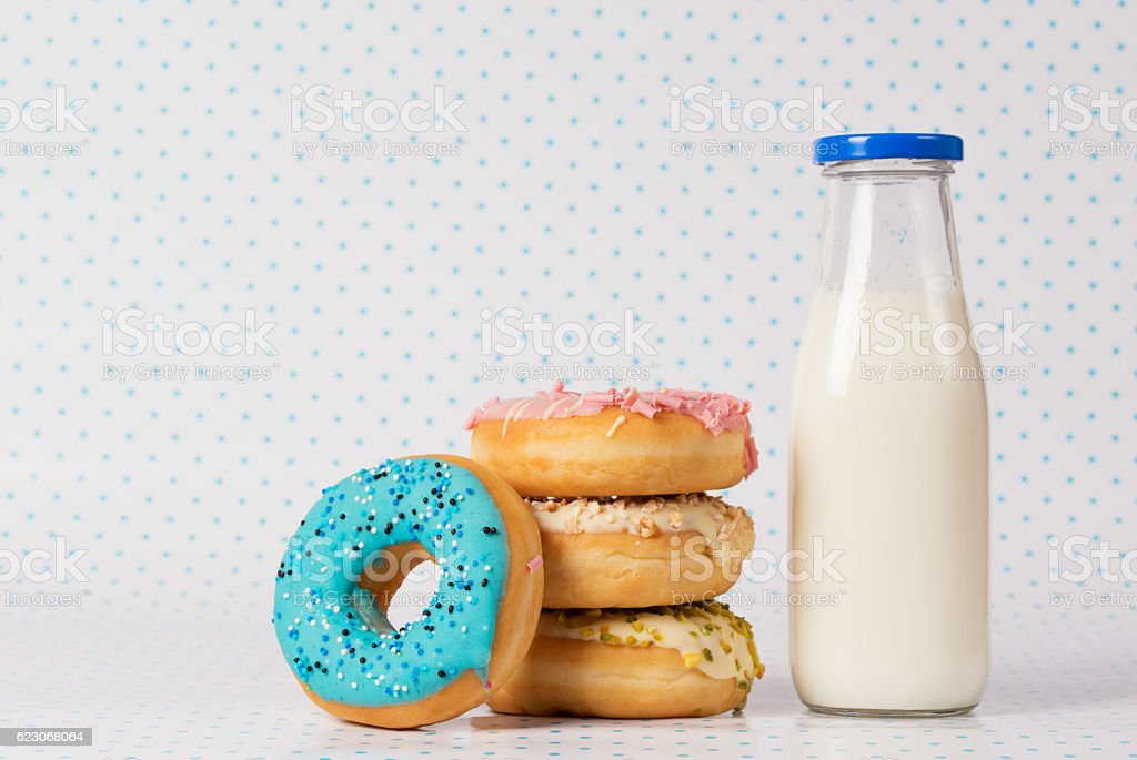 Pile of colored donuts, blue donut and bottle of milk stock photo