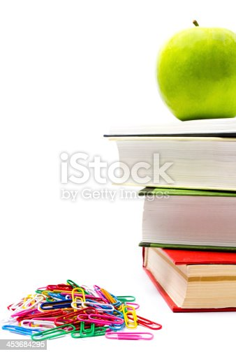 istock Pile of colorful books and apple on white background. 453684295