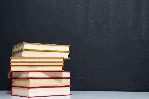 pilha de livros coloridos no fundo do quadro-negro - foto de acervo