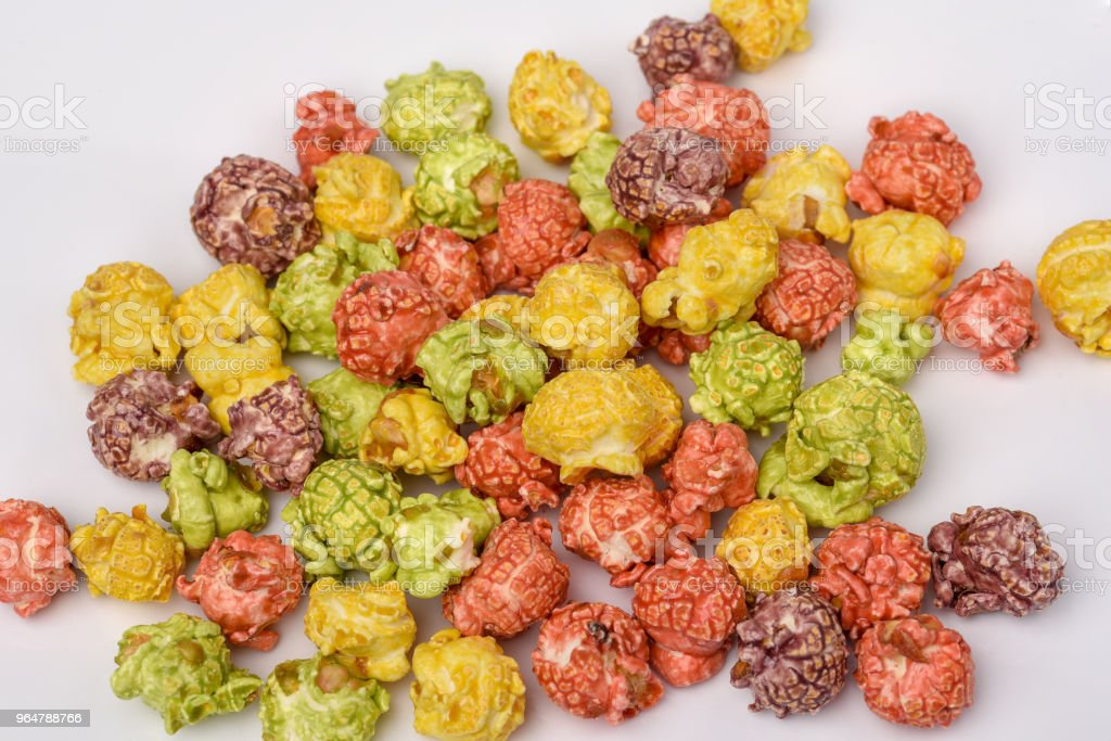 A pile of colorful caramel popcorn, still life for a holiday with colorful popcorn on white wooden table royalty-free stock photo