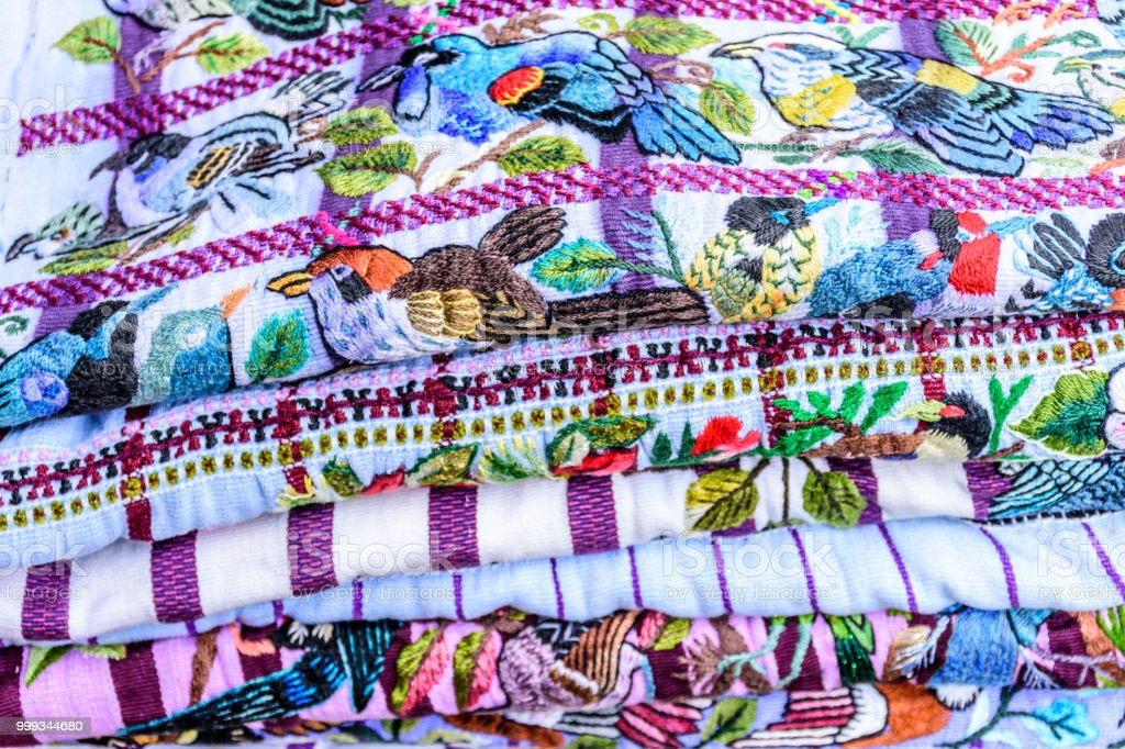 Pile of colorful blouses called huipil with hand embroidered birds &...