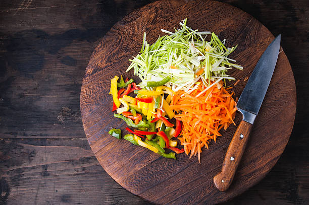 Pile of colorful vegetables on a wooden board with knife stock photo