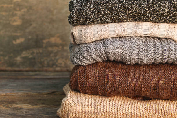 Pile of colorful warm clothes on wooden background. Pile of colorful warm clothes on wooden background. coat garment stock pictures, royalty-free photos & images