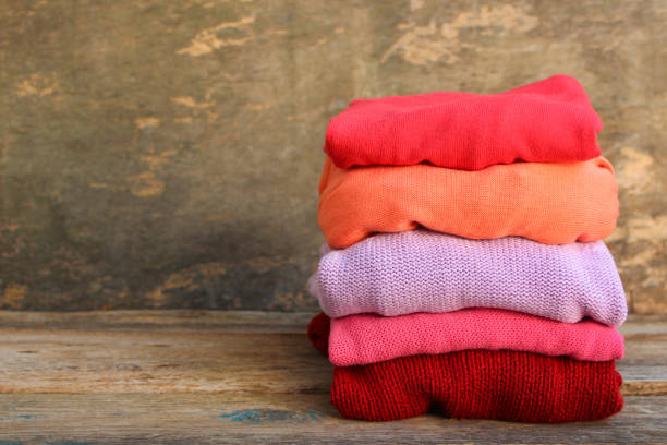 Pile of colorful warm clothes on wooden background. Toned image. Pile of colorful warm clothes on wooden background. Toned image. coat garment stock pictures, royalty-free photos & images