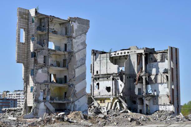 ein haufen von konkreten rückstand auf dem hintergrund eines großen zerstörten gebäudes. hintergrund. - betonwerkstein stock-fotos und bilder