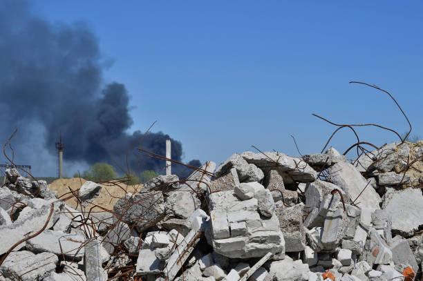 ein haufen von betonbruch mit bewehrung auf dem hintergrund der dicken schwarzen rauch in den blauen himmel ragt. - betonwerkstein stock-fotos und bilder