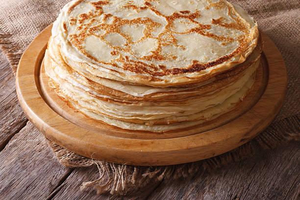 haufen von crêpes mit küche auf den tisch. horizontale bord - buchweizenpfannkuchen stock-fotos und bilder