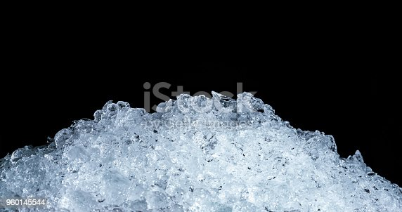 Pile of crushed ice cubes on dark background with copy space. Crushed ice cubes foreground for beverages.