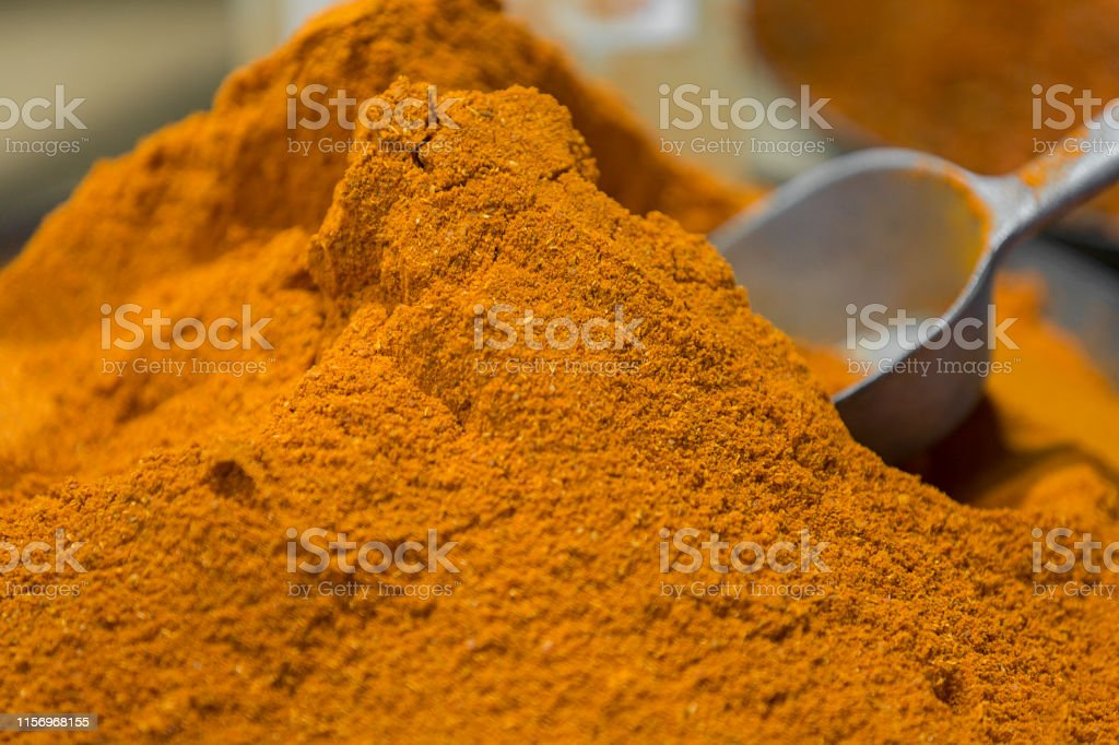 Pile of curry powder with a metal spoon