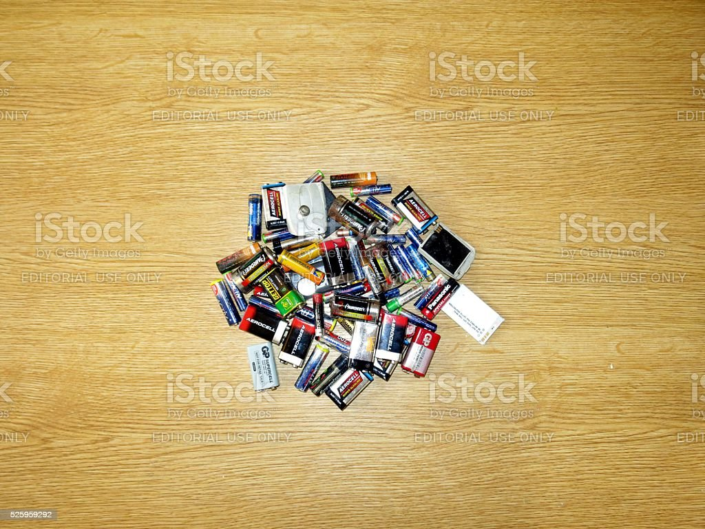 Pile of dead batteries on wooden board stock photo