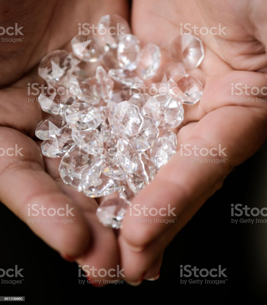 Pile of diamonds in woman hands stock photo