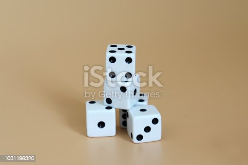 istock A pile of dice with a soft brown background. 1031196320