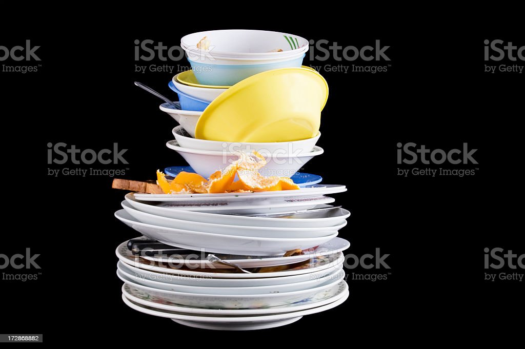 Pile of dirty dishes with an orange rind and rotting food stock photo