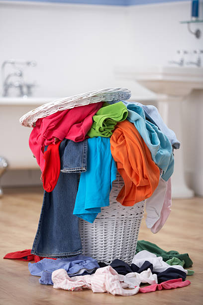 Pile of dirty washing in bathroom Pile of dirty washing overflowing laundry bin in bathroom laundry basket stock pictures, royalty-free photos & images