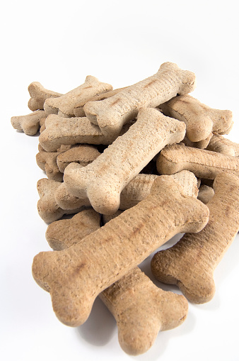 Vertical Digital Color Photograph of a Pile of Bone Shaped Dog Cookies against a White Background taken in studio.