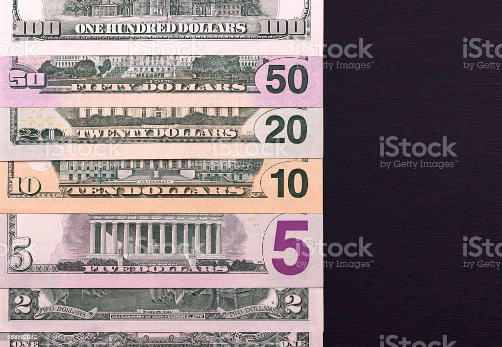 Pile of dollar bills of different denominations on black backgrond. stock photo