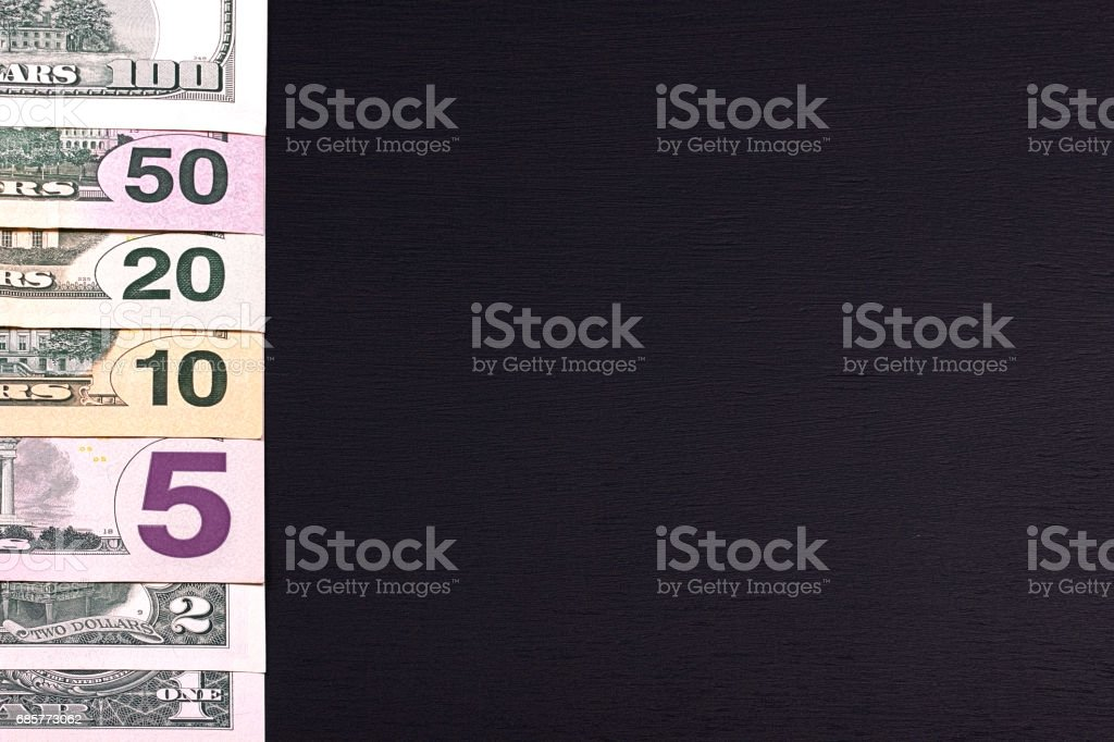 Pile of dollar bills of different denominations on black backgrond. royalty-free stock photo