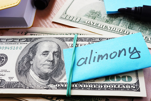 istock Pile of dollars with word alimony on a stick. 888977718
