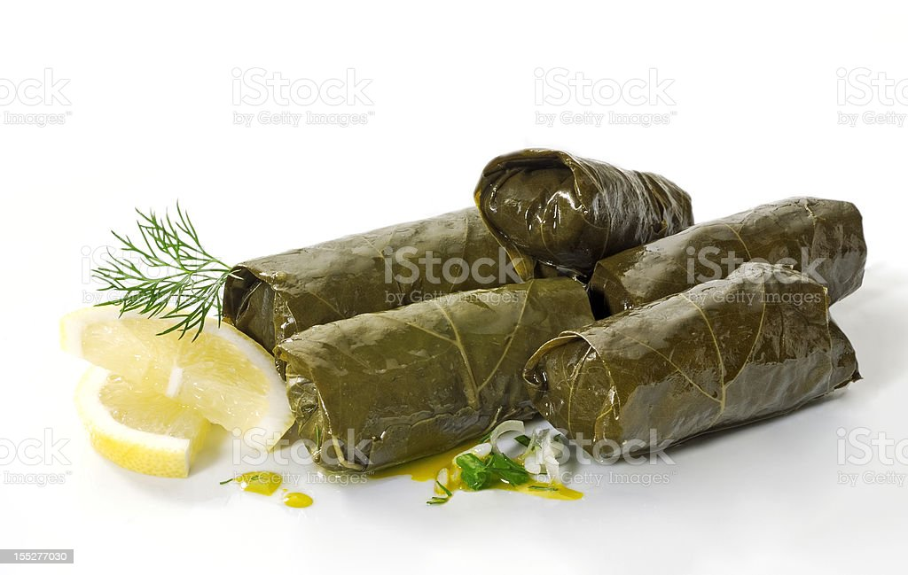 A pile of dolmades with lemon on a white background stock photo