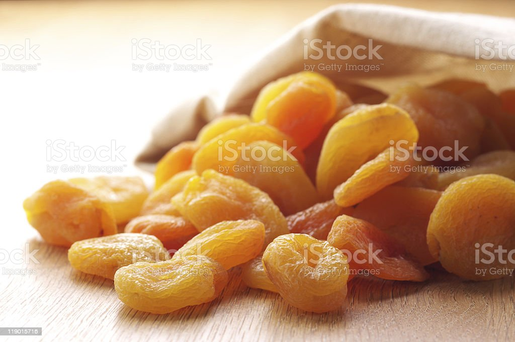 A pile of dried apricots on a wooden surface stock photo