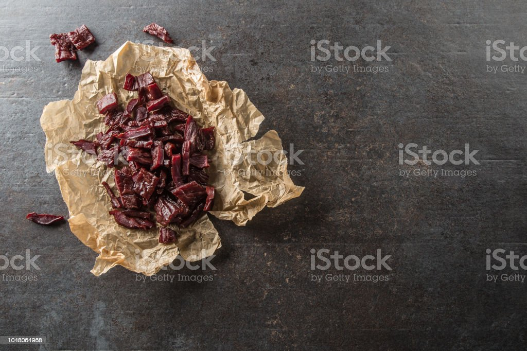 A pile of dried beef jerky pieces on paper and cutting board. stock photo