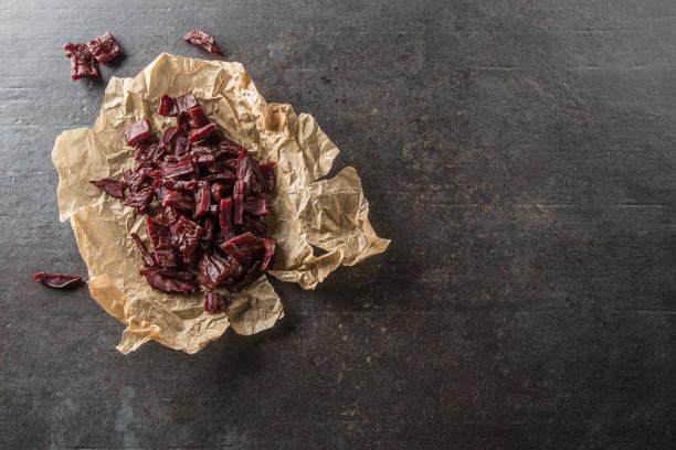 Ein Haufen getrocknetes Rindfleisch ruckartig Stücke auf Papier und Schneidebrett. – Foto