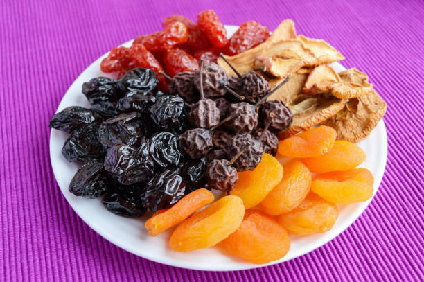a pile of dried fruits (apples, prunes, apricots, pears, cranberries) on a white plate on a purple background. antioxidant mix. a useful product. proper nutrition. harvest. - dried fruit stock photos and pictures