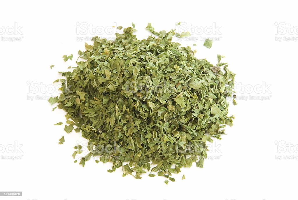 Pile of dried parsley leaves on white royalty-free stock photo