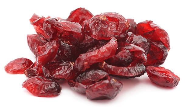 pile of dried shriveled red cranberries on white background - gedroogd voedsel stockfoto's en -beelden