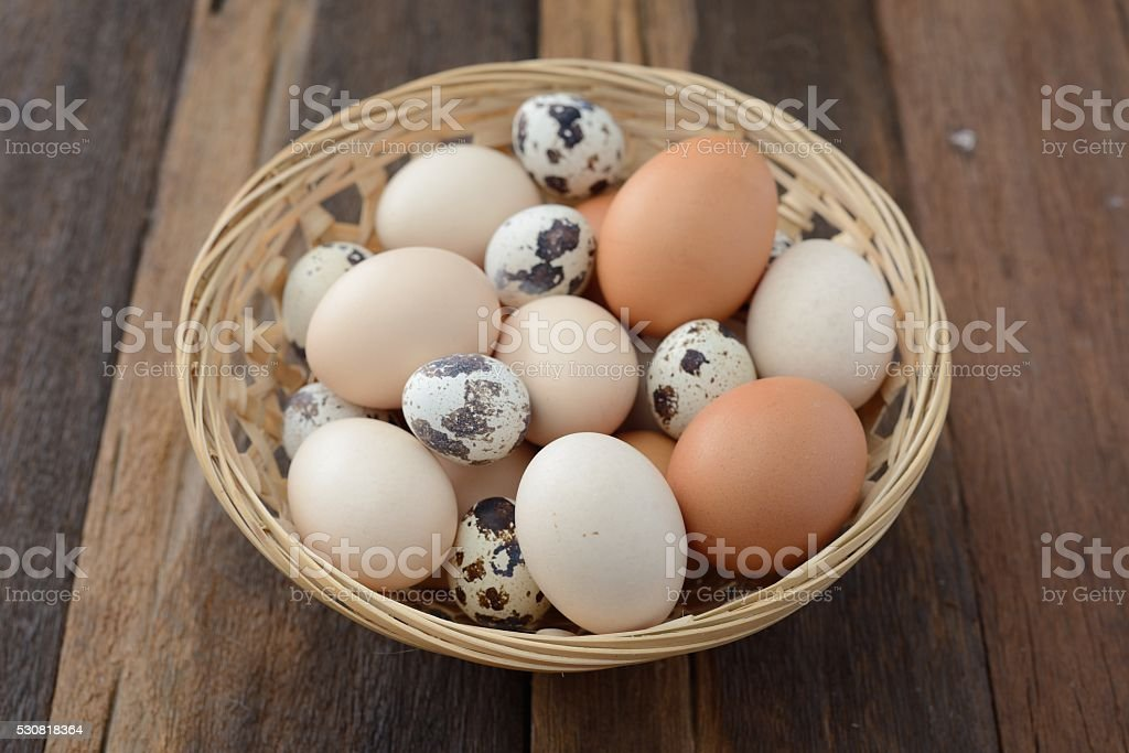 Pile of farm-fresh brown eggs sits in a brown basket stock photo