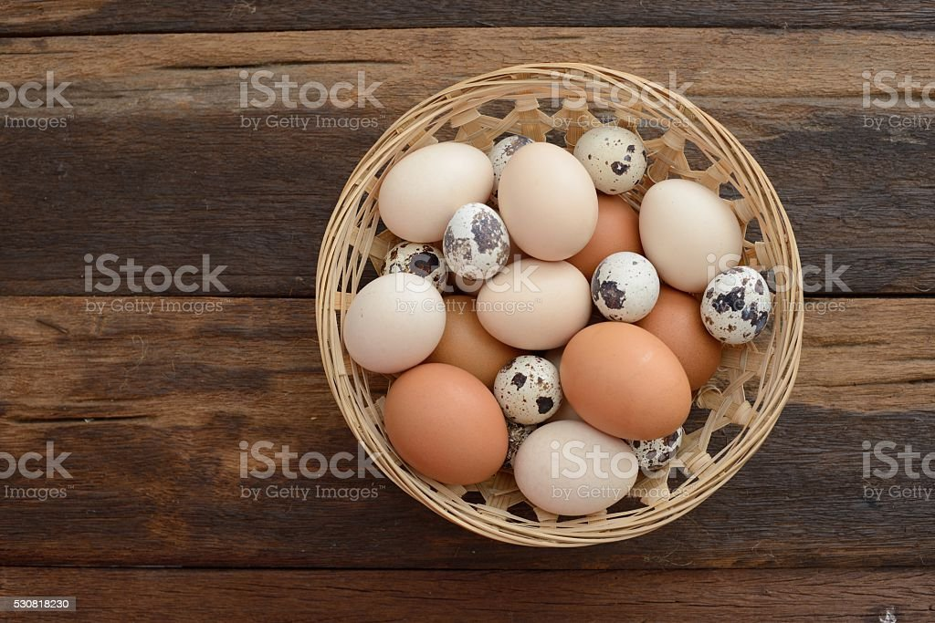 Pile of farm-fresh mix eggs sits in a brown baske stock photo