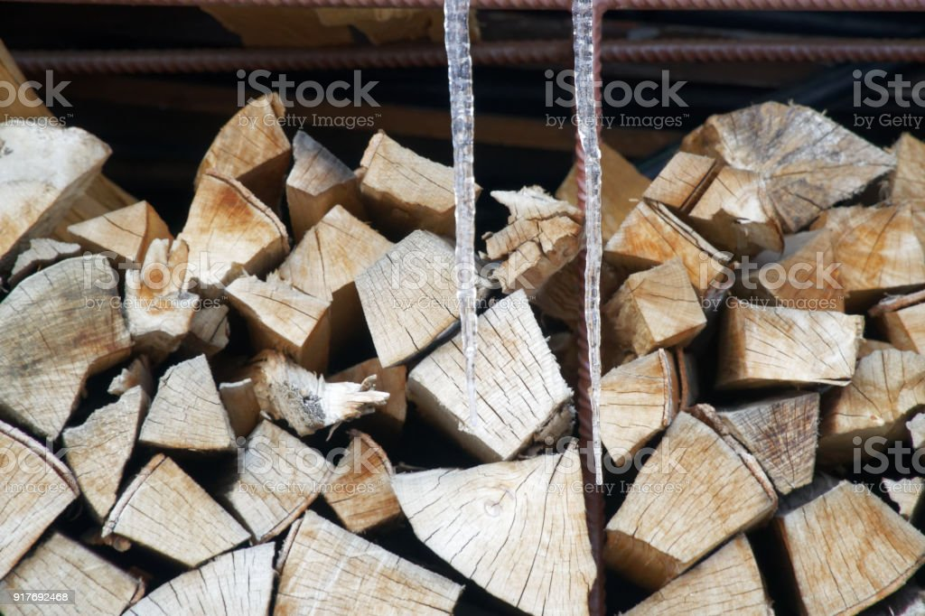 Pile of firewood and icicle in winter season Wooden background stock photo