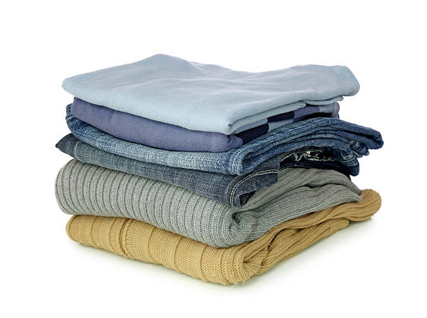 pile of folded clothes on a white background - folded stock photos and pictures