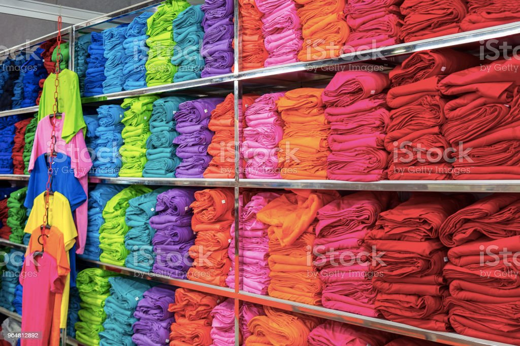 Pile of folded colourful t-shirts clothes in a shop. royalty-free stock photo
