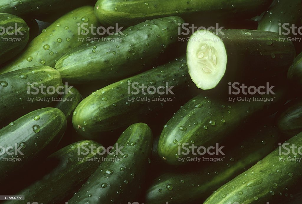 Pile of fresh cucumbers with one cut open stock photo
