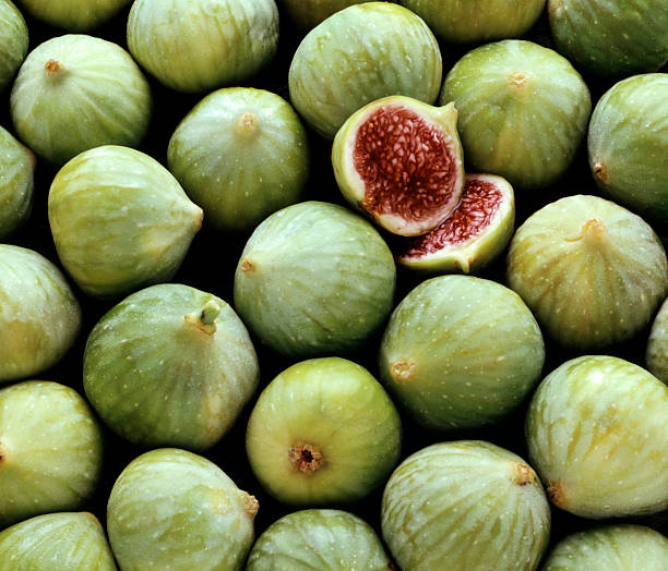 Pile of fresh green figs, one cut open stock photo