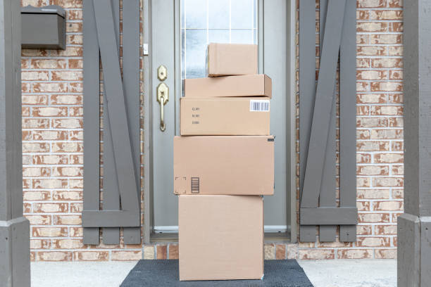 Pile of Freshly delivered Boxes being left outside at front door stock photo