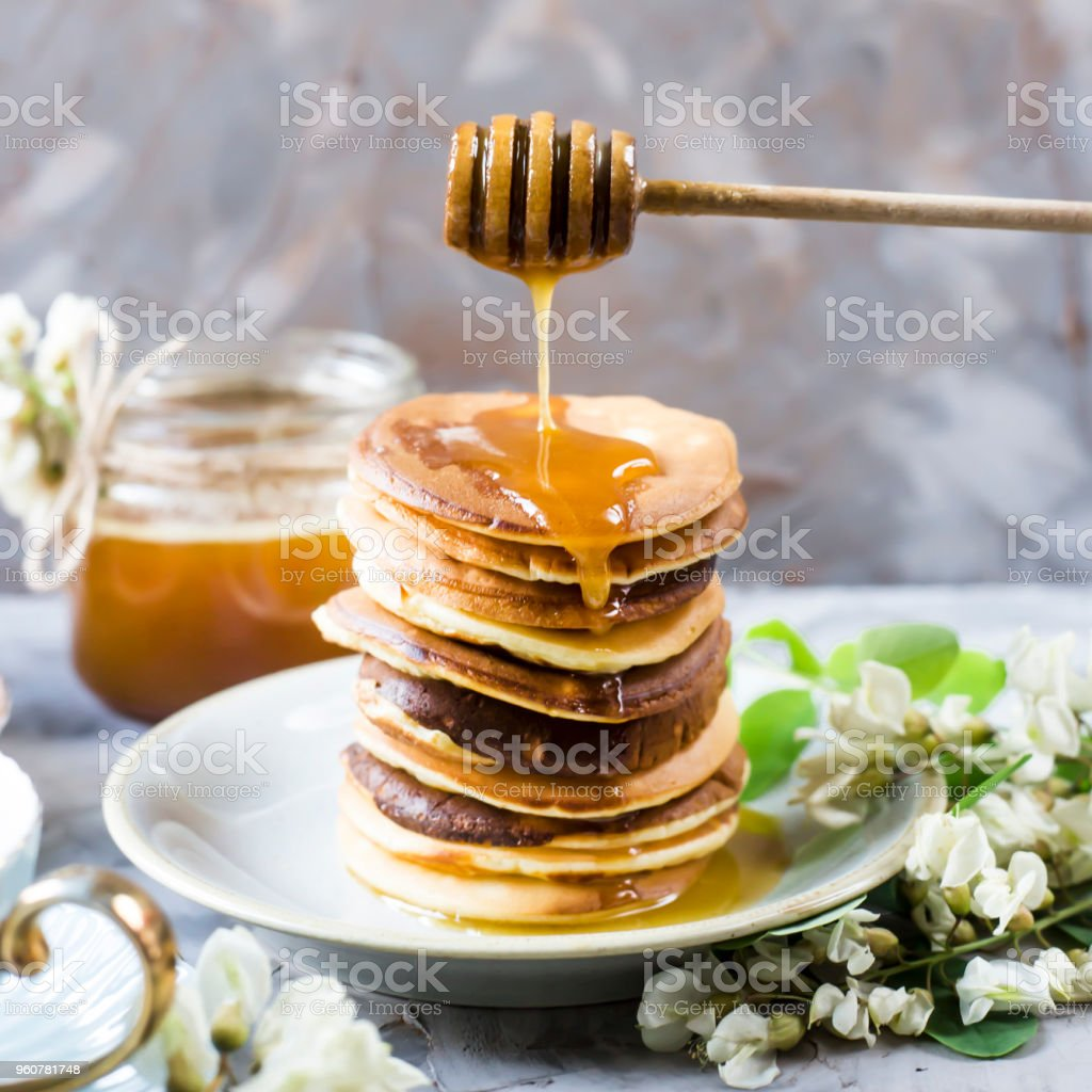 A Pile Of Fritters Next To A Cup Of Tea And A Jar Of Honey On A Gray