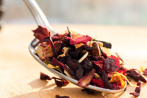 Pile of fruit tea with petals and dry fruit .The composition of the heap of tea leaves and dried hibiscus flower located on a wooden Board. Tea with natural ingredients closeup. Macro photo of tea.