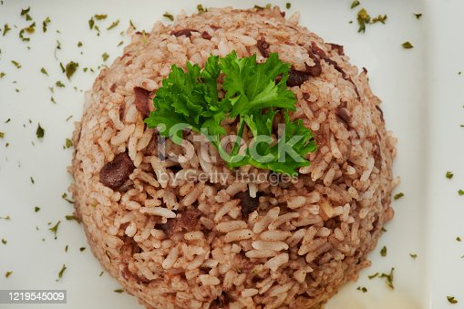 Pile of gallo pinto rice with parsley on plate close up view