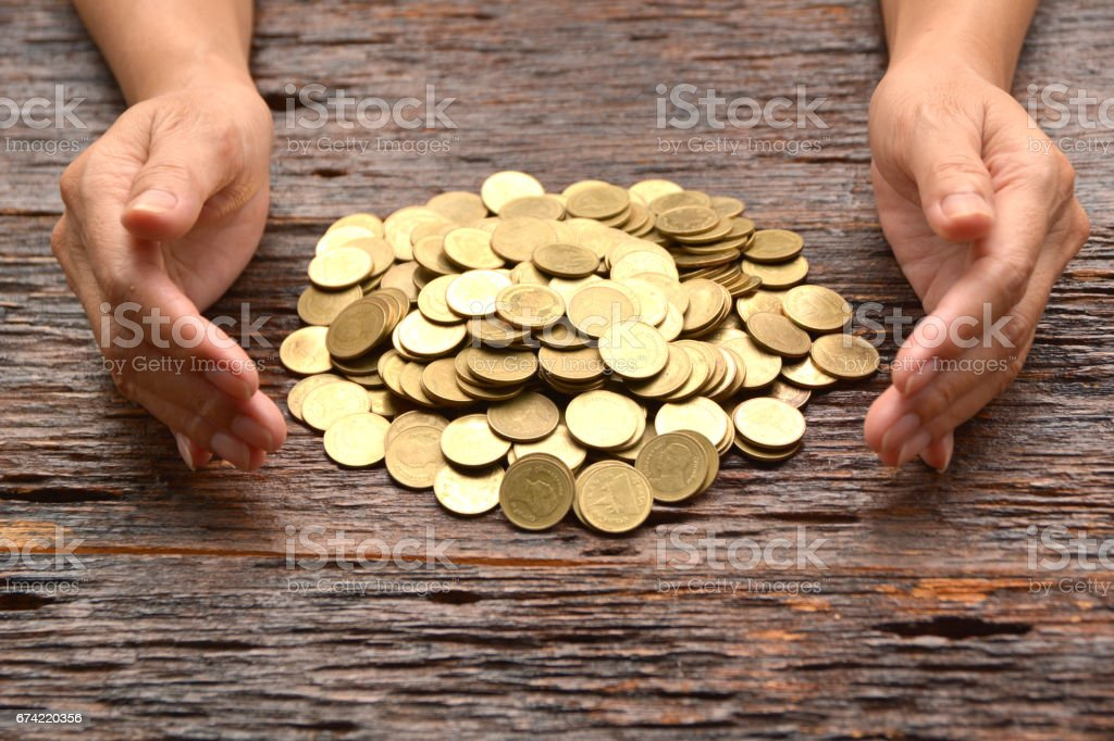 pile of gold coin with woman hand financial concept. stock photo