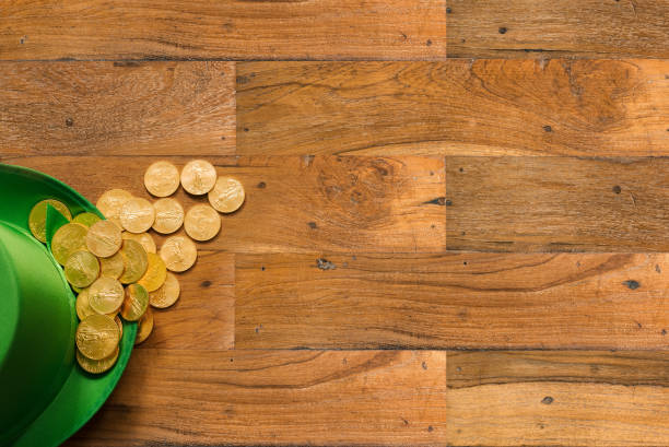 pile of gold coins inside green hat st patricks day - happy st. patricks day stock photos and pictures