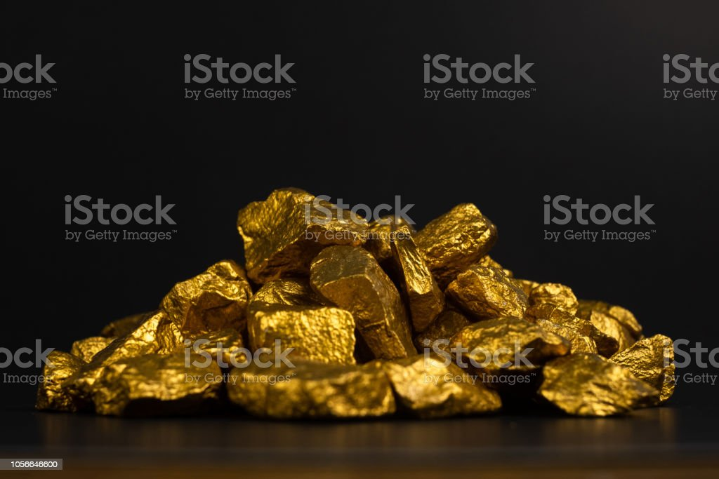 A pile of gold nuggets or gold ore on black background, precious...